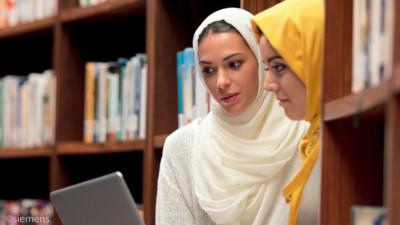 Zwei Frauen mit Hijab in einer Bibliothek